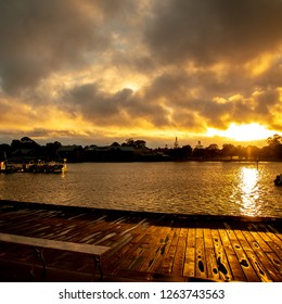 Sun rising over the estuary in Mandurah, Western Australia with a moody stormy cloud filled sky, beautiful colours and reflections.
