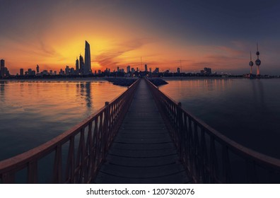 Sun rising over kuwait  city skyline