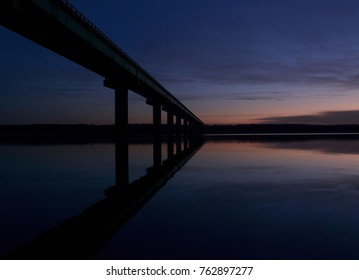 The sun is rising over a Midwest lake. A mile long bridge soars over the water, creating a reflection on the blue lake.