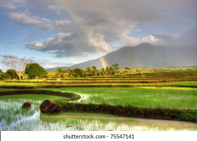 Sun rising over a rice field in the Philippines with a double rainbow and mountain in the background.