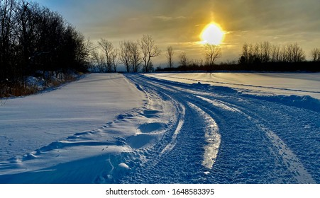 The sun was rising and the reflection was iridescent in the snow. The snowmobiles pass in a field, they have beautiful landscapes. Ulverton, Quebec, Canada; February 15, 2020.