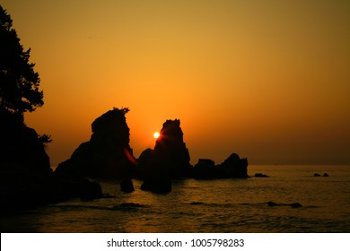 The sun rising in the sea between the rocks