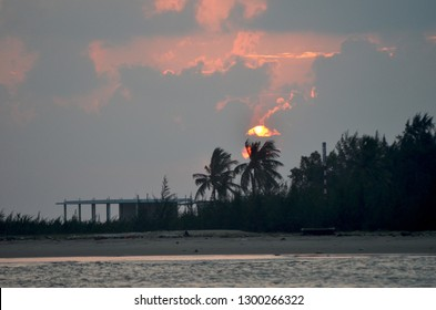 The sun is rising through clouds. The sky is orange while the clouds are grey in colour. A beach with a shack and plam trees remain in darkness.