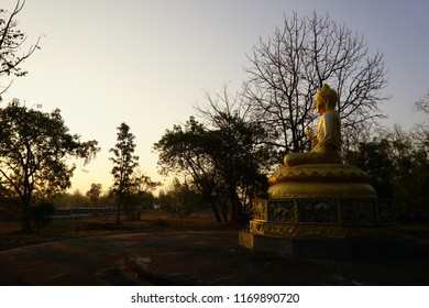 The sun is rising from the trees. Morning light struck the Buddha beautifully. The power of peace, faith in the temple in Thailand.