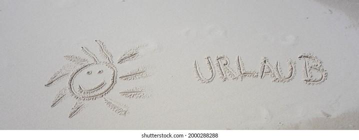 "Sun in Sand with Word Holidays german ""Urlaub"" - Shutterstock ID 2000288288"