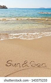 Sun and sea written in a sandy tropical beach