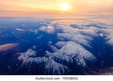 sun set top view of mountains with snow and clouds.
