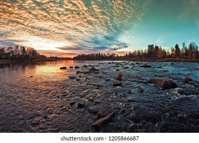 The sun sets beautifully behind the horizon on an autumn evening at the Northern Finland. The rocks in the river form interesting patterns in the flowing water.