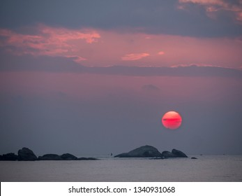 the sun sets and becomes a red ball over the rocks of the indian ocean.