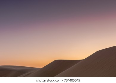 The sun sets behind the desert dunes creating a beautiful contrast of color and media, showing that the desert isn't all sand