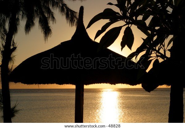 The sun sets behind a grass shelter on the paradise island of Mauritius.