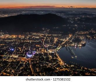 The sun sets behind the hills of Como, Italy as the holiday lights of the Como Magic Light Festival/Città dei Balocchi illuminate the city, as seen from the top of the Funiculare di Como in Brunate.