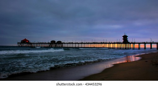 The sun sets behind the Hunting Beach Pier in Hunting Beach Ca