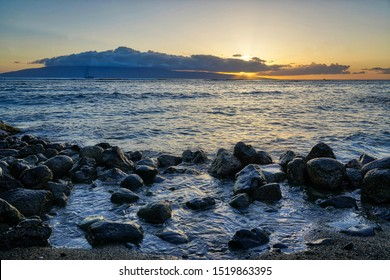 The sun sets behind Lanai as seen from the beach in Lahaina.
