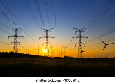 the sun sets behind the lines of hydro towers with one lonely windmill on the side, in the Southern Bruce Peninsula.