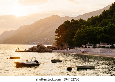 The sun sets behind the mountain before sunset in Brela, Croatia. Boats in the sea illuminated by light.