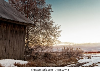 The sun sets behind an old barn house at the rural Finland. The day was cold, but there wasn't much snow on the ground.