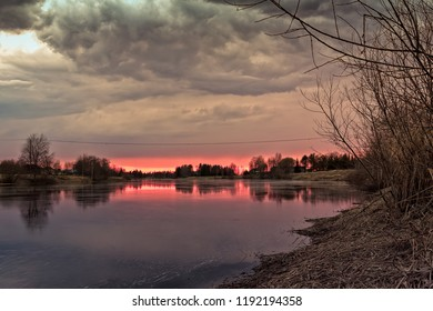 The sun sets behind the river bend and colors the dramatic clouds of the sky red. This is spring in the Northern Finland.