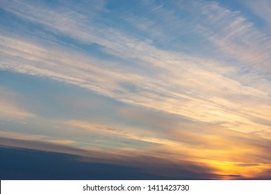 the sun sets in clouds in the form of tracks. sunset light. clouds in the form of long orange stripes on the sky.