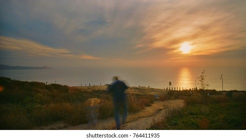 The sun sets in the distance as the silhouettes of a father and his daughter walk towards the lookout over Torrey Pines, California.