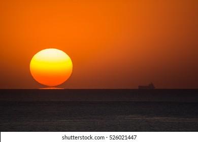 Sun sets near a fade silhouette of a ship on the horizon