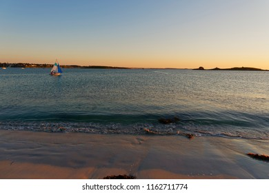 As the sun sets on a beach at Landeda, Brittany, a small sailing boat is out on the calm water