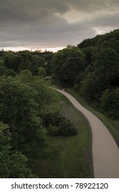 The sun sets on a cloudy evening over Jesmond Dene in Newcastle upon Tyne, England. Photograph taken from the Armstrong Bridge.