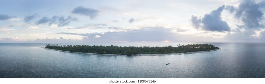 The sun sets on an idyllic tropical island in Wakatobi National Park, south of Sulawesi in Indonesia. This beautiful region harbors amazing coral reefs and a wide array of marine life.