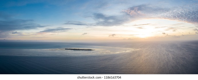 The sun sets on an idyllic, tropical island in Wakatobi National Park, Indonesia. This area is home to amazing, biodiverse coral reefs and is a popular destination for scuba divers and snorkelers.