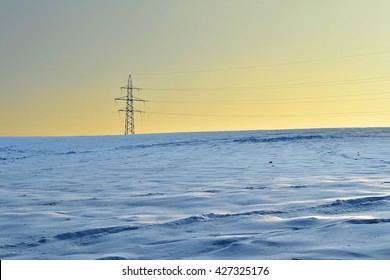 The sun sets on a snowy field with high tension wires.