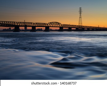 The sun sets over a bridge as a river flows in the foreground.