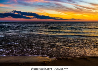 The sun sets over a calm and peaceful Lake Michigan at Grand Haven, Michigan