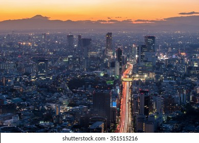 The sun sets over the cityscape of Tokyo, with Mount Fuji.