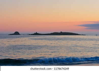 The sun sets over a clam sea, small waves breaking, behind a small rock island in the bay