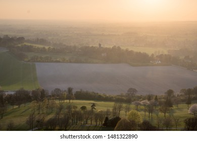 The sun sets over fields and villages in the agricultural landscape of the Aylesbury Vale, including the tower of the parish church of Ellesborough.