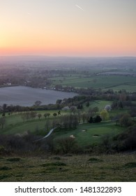 The sun sets over fields and villages in the agricultural landscape of the Aylesbury Vale, viewed from Combe Hill on the scarp of the Chiltern Hills.