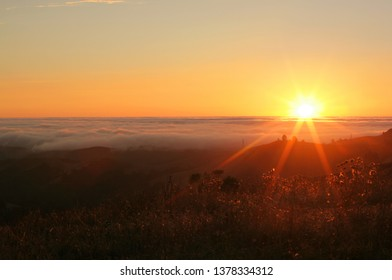 The sun sets over a fog-covered Pacific Ocean, as seen from Windy Hill, a crest in California's Santa Cruz Mountains