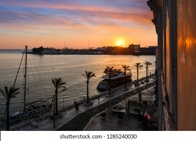 The sun sets over the harbor port as boats dock along the waterfront promenade in the coastal city of Brindisi, Italy, in the Puglia region