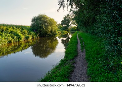 As the sun sets over the landscape a well worn tow path runs beside the calm, still water of the Shropshire Union Canal neat Whitchurch.