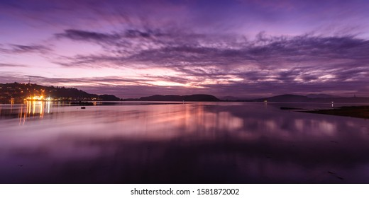 Sun sets over Oban Bay in the West Highlands of Scotland, including the lights of Oban town and the coast of Kerrera island.