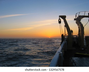The sun sets over the Pacific Ocean as viewed from the back of a trawling vessel.