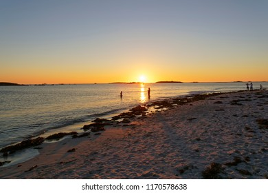 As the sun sets over Plage Sainte-Marguerite, Brittany, two people stand in the Celtic Sea, three more stand on the shoreline.