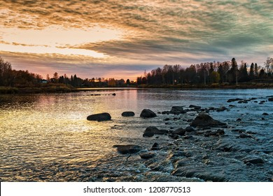 The sun sets over the rocks of a river in the Northern part of Finland. The colors of the autumn sky are pretty dramatic.