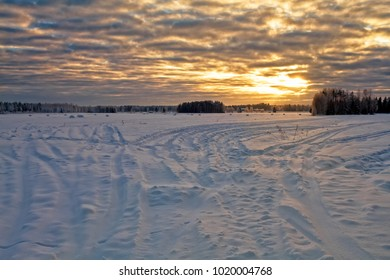 The sun sets over the snowy fields on a very cold day in the Northern Finland. The tractor tracks lead to the hay rolls covered with snow.