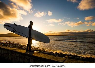 Sun sets as a surfer looks at the ocean.  Strandhill.  Sligo.  Ireland.