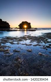 The sun sets through an arch near Blairgowrie in Victoria, Australia.