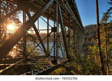The sun sets from under the old steel cantilever bridge across Deception Pass in Oak Harbour, Washington