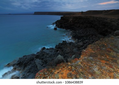 The sun sets and waves crash on the rocky shore of South Point Hawaii - The Southernmost Point on the Big Island of Hawaii