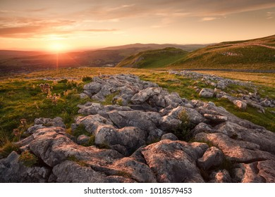 The sun sets in the Yorkshire Dales high in the hills amongst the limestone pavement
