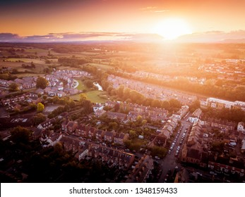 Sun setting with atmospheric effect over traditional British houses and tree lined streets. Dramatic, warm lighting creates a homely mood. Very typically English houses that are over 100 years old.